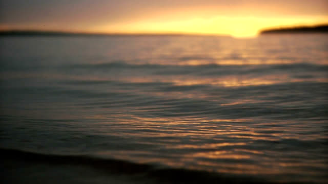 vídeos de stock e filmes b-roll de perto de foco de ondas ao pôr do sol - margem do lago