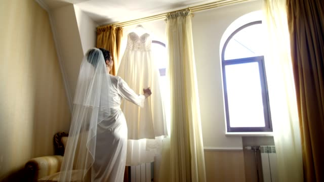 near window, in room, white wedding dress hanging on the window eaves. the bride, a beautiful girl in a white peignoir, a bathrobe, is considering her wedding dress, preparing for the wedding