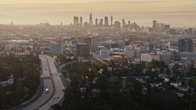 vídeos de stock e filmes b-roll de near-empty freeway with los angeles cityscape at dawn during covid-19 lockdown - aerial shot - covid flight