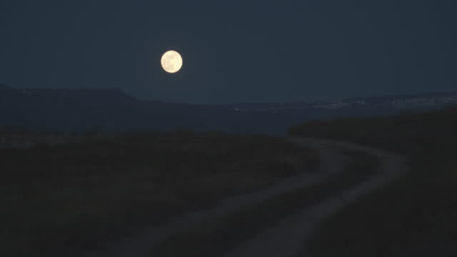 A Nearly Full Moon Rises Over the Grand Mesa Overlooking Grand Junction, Colorado with a Dirt Road in the Foreground