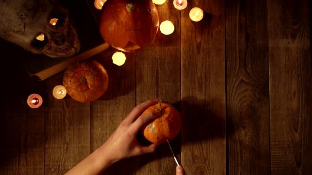 neat cutting of a pumpkin lantern for the halloween holiday top view - zucca legenaria video stock e b–roll