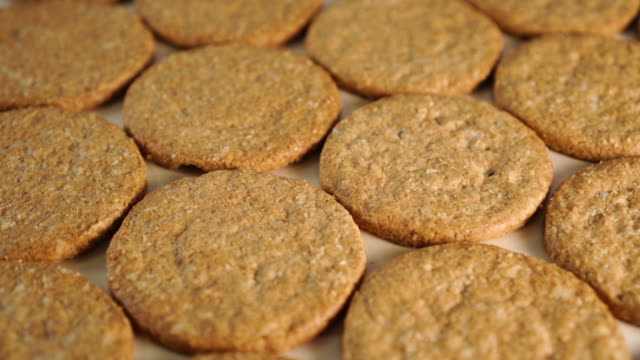 Neatly folded oatmeal cookies rotate on a wooden board Neatly folded oatmeal cookies rotate on a wooden board. Making a healthy breakfast cookie stock videos & royalty-free footage