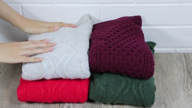 Neatly folded winter clothes. Folding sweaters in a pile. Cozy sweaters are lying in a pile. A female hand on stacks warm sweaters in pile. Female stacking the warm sweaters into the pile. Neatly folded winter clothes. Folding sweaters in a pile. Cozy sweaters are lying in a pile. A female hand on stacks warm sweaters in pile. Female stacking the warm sweaters into the pile. heap stock videos & royalty-free footage