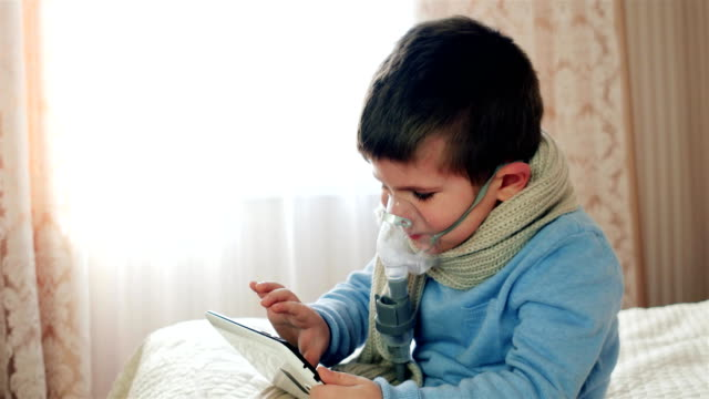 vídeos de stock e filmes b-roll de nebulizer for inhalation, kid with an oxygen mask on his face plays on the tablet, sick child breathes through nebulizer, boy does inhalation, treatment at home - oxigénio fenómeno natural