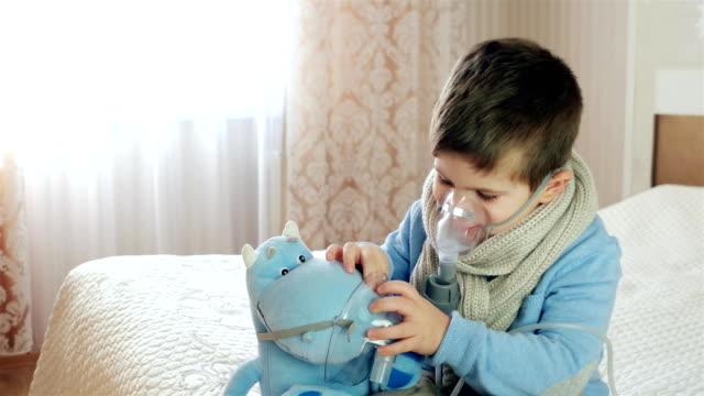 vernebler zur inhalation, kranke kind atmet durch vernebler, baby tut inhalation, junge mit einer sauerstoffmaske auf seinem gesicht, behandlung zu hause - sauerstoff stock-videos und b-roll-filmmaterial