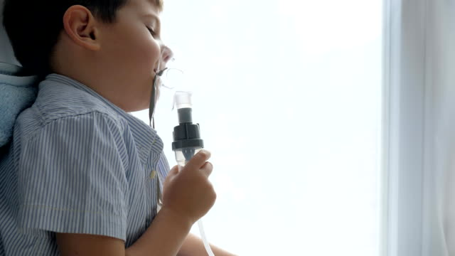 nebulizers therapy, diseased boy breathes through an inhalant for treatment in hospital - neonati maschi video stock e b–roll
