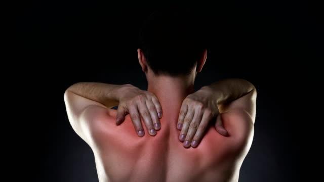 Douleur au cou, l'homme avec le mal de dos sur fond noir - Vidéo