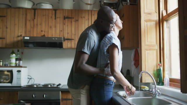Need any help with those? 4k video footage of a woman washing dishes while her husband embraces her from behind washing dishes stock videos & royalty-free footage