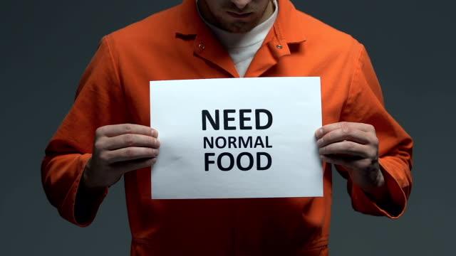 need normal food phrase on cardboard in hands of caucasian prisoner, protest - wine filmów i materiałów b-roll
