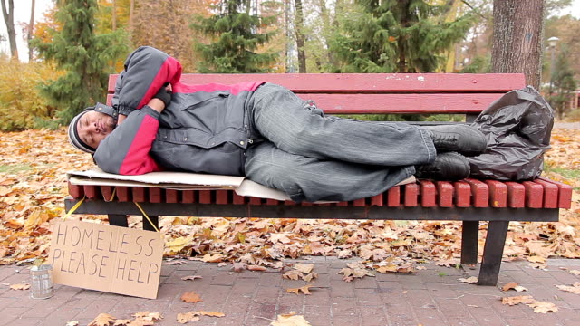 Needy male sleeping on bench in autumn park, homeless man waiting for help video