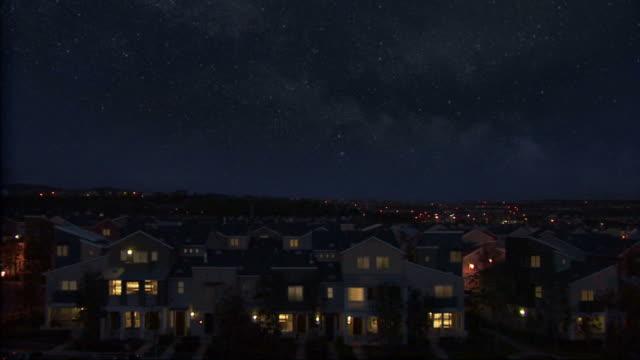Neighborhood at night with shooting star.