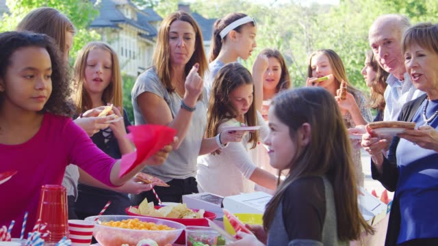 neighbours stand eating at table at a block party, close up - vicino video stock e b–roll
