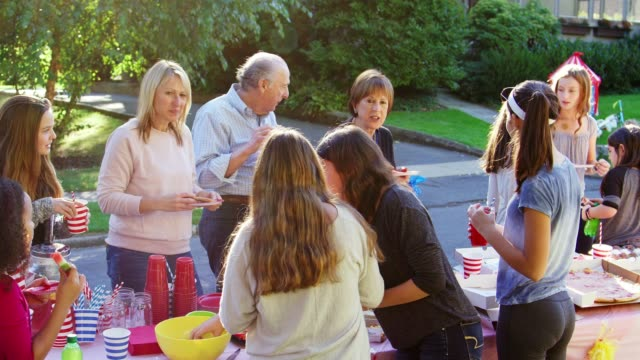 neighbours stand talking and eating at a block party - vicino video stock e b–roll