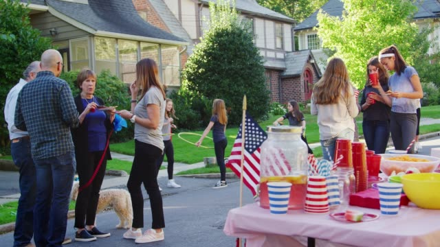 neighbours talk, eat and play at a block party - vicino video stock e b–roll