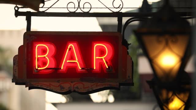 vídeos de stock e filmes b-roll de neon bar sign hangs from a drinking establishment - bar local de entretenimento