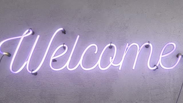 neon-zeichen rechtschreibung das wort willkommen dieses realistische zeichen beginnt, wenn das zeichen ausgeschaltet ist, dann schaltet es sich mit erstaunlich blinkenden flackernden effekten, dann nach 30 sekunden blinkt es ein und aus - welcome stock-videos und b-roll-filmmaterial