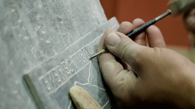 Nepalese craftsman working on traditional Mani slate stone in Kathmandu, Nepal.