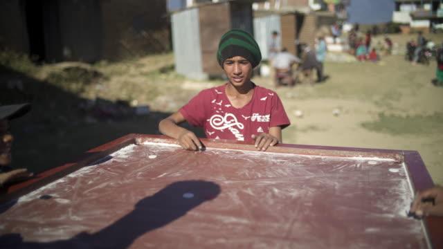 ネパールの少年再生キャロム屋外 - ネパール点の映像素材/bロール