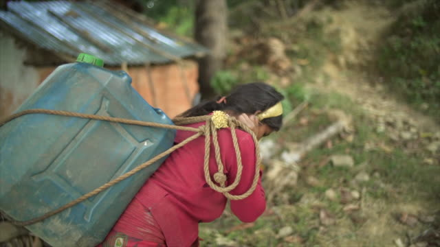 Nepali girl carries large jug of water with head strap Hand-held camera view poverty stock videos & royalty-free footage