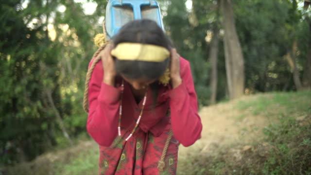 ネパール人少女を運ぶ水上り坂の大規模な水差し - ネパール点の映像素材/bロール