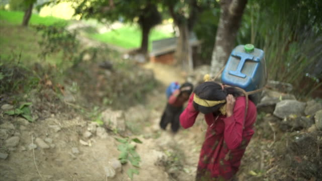 Nepali girls carry large jugs of water uphill Hand-held camera view poverty stock videos & royalty-free footage