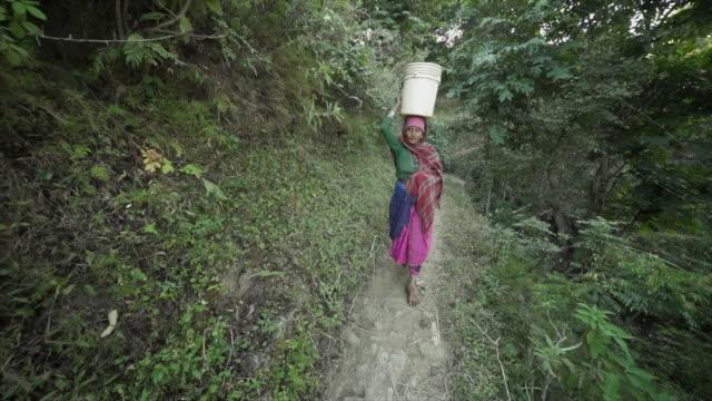 ネパールの女性が狭い未舗装の道の頭の上にプラスチック製のバケツを運ぶ - ネパール点の映像素材/bロール