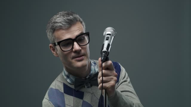 Nerd guy adjusting the microphone before giving a speech