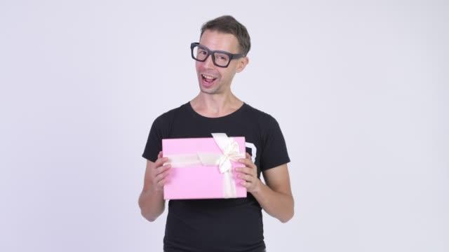 Homem do lerdo com os eyeglasses que prendem a caixa de presente - vídeo