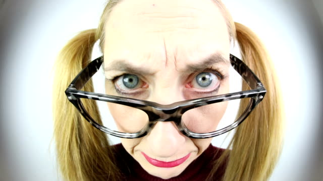 Nerdy Stern Face Looking Over Glasses A close up fisheye video clip of a nerdy woman with a stern expression. wide angle stock videos & royalty-free footage