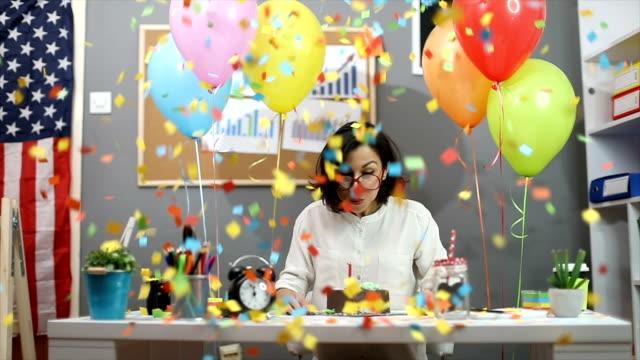 Nerdy mujer soplando velas en un cumpleaños en la oficina - vídeo