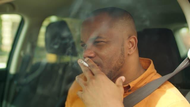 nervoso autista maschio africano fuma sigaretta in auto - sigaretta video stock e b–roll