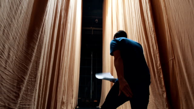 Nervous and mad actor behind curtains There is one young man, age 23. He is in theater and he have a rehearsal. He is an actor,he read and learn his text. performer stock videos & royalty-free footage