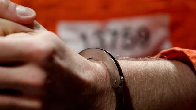 vidéos et rushes de mains criminelles nerveux lors d'amnesty, prisonnier numéro jumpsuit closeup - meurtre