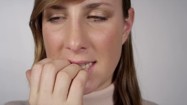 CLOSE UP: Nervous female biting her nails video