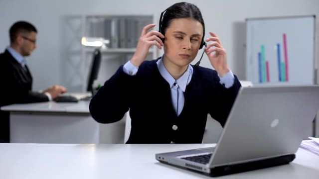 Nervous female call manager taking off headset and closing laptop, hard day
