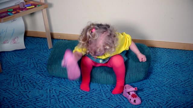 vídeos y material grabado en eventos de stock de chica nerviosa jugando con sus zapatos. niño puede colocar sandalia en - moda playera