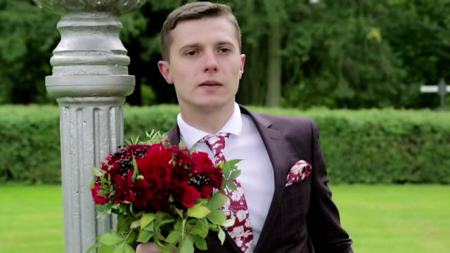 A nervous groom with a bouquet waiting for his bride. Slow motion. video