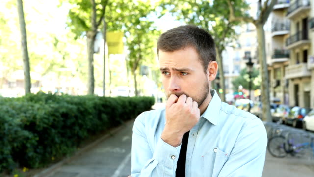 Nervous man biting nails looking away in the street