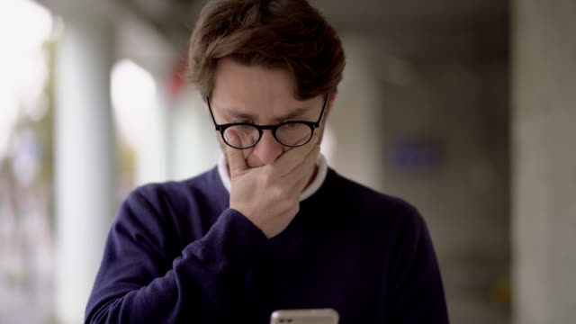 Nervous man in eyeglasses using smartphone outdoor