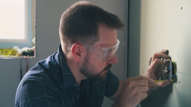 vídeos de stock e filmes b-roll de nervous man repairs plug on wall with screwdriver in room - obras em casa janelas