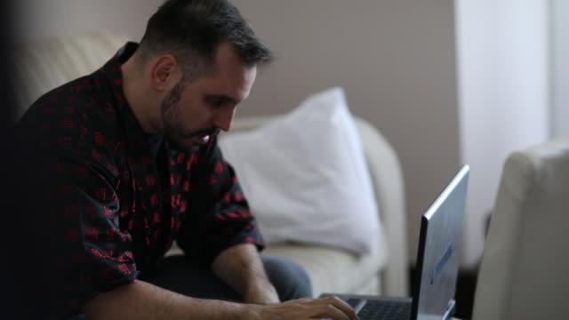 nervös man sitter på bäddsoffa och använder laptop på hotellet - endast en man i 30 årsåldern bildbanksvideor och videomaterial från bakom kulisserna