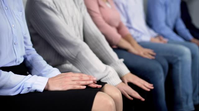 nervöse menschen sitzen in warteschlange am krankenhaus, stressigen momente, schlechter service - abwarten stock-videos und b-roll-filmmaterial
