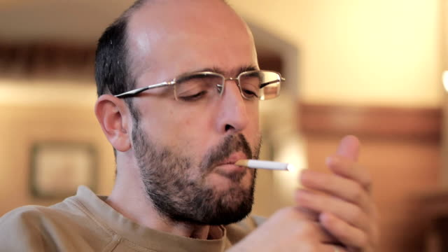 Nervous, tensed, bold man with glasses smoking cigarette, drinking coffee video