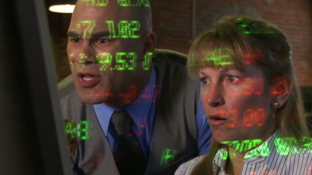 Nervous Traders Two city types look nervous and start to panic on their phones as stock market ticker symbols are projected across them.  Man uses a phone and computer.  Woman in background uses a tablet computer.  Medium shot with dolly move past computer screen.  All ticker symbols are fictitious companies. financial occupation stock videos & royalty-free footage