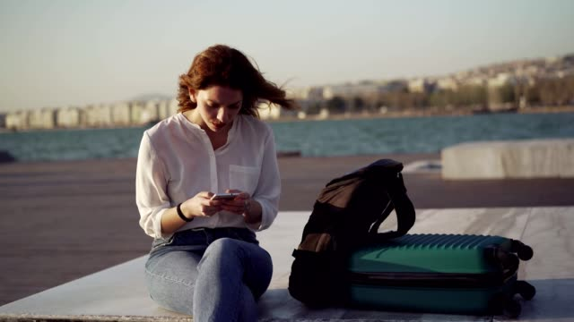 Nervous woman expecting a phone call Young woman is sitting worried and nervous by the sea with suitcase and texting messages. impatient stock videos & royalty-free footage