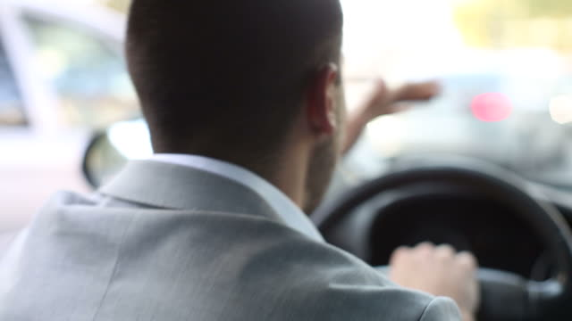 Nervous young businessman in a car honking the horn in traffic