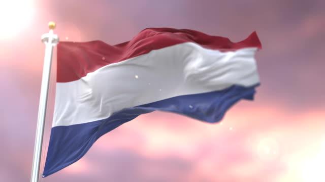 stockvideo's en b-roll-footage met nederlandse vlag zwaaien op wind bij zonsondergang in traag, lus - maastricht