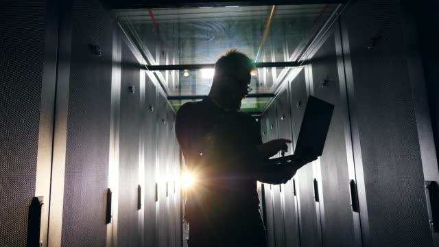 it network security concept. backlit male engineer is working with a laptop - podświetlony filmów i materiałów b-roll