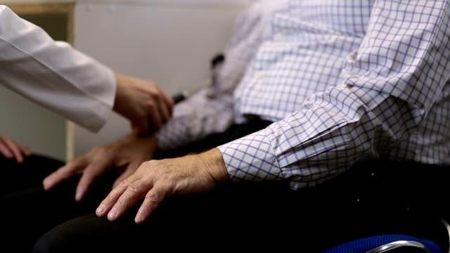 Neurologist checking arm reflex of male patient video