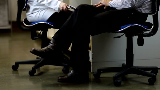 Neurologist testing knee reflex of male patient video
